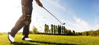 Golfer hitting a golf ball with grass flying