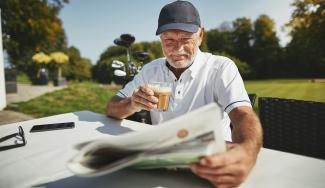Senior golfer reading the news paper and drinking coffee